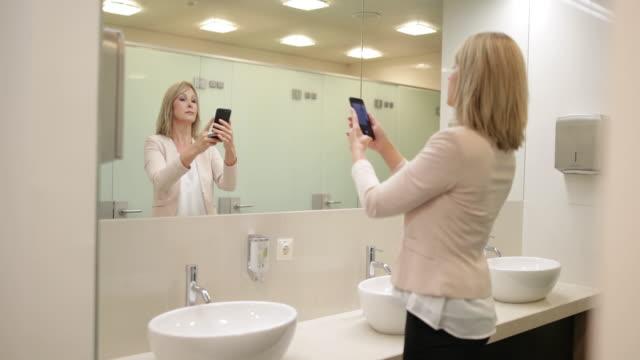 vidéos et rushes de businesswoman using a smartphone as a mirror - salle de bains et toilettes