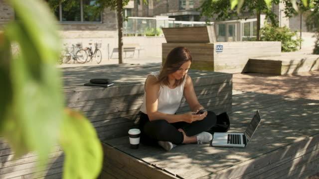 affärskvinna med hjälp av en smartphone - student bildbanksvideor och videomaterial från bakom kulisserna
