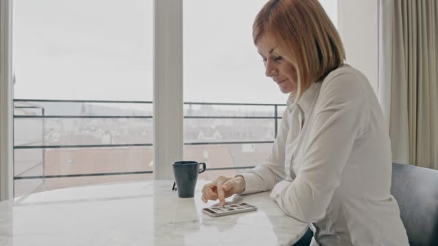 ws businesswoman using a smartphone while drinking a coffee at home - after work stock videos & royalty-free footage