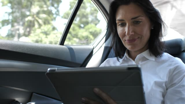 businesswoman using a tablet while sitting in the back seat of the car - adult stock videos & royalty-free footage