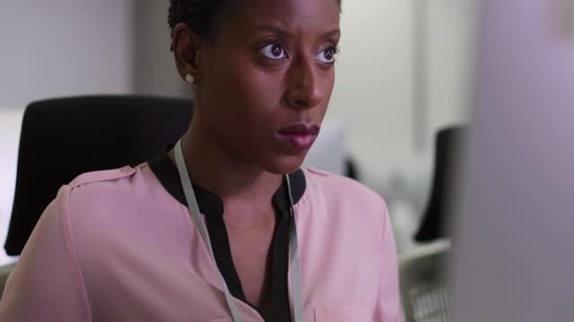 vidéos et rushes de businesswoman using computer in empty office - rouge à lèvres rouge