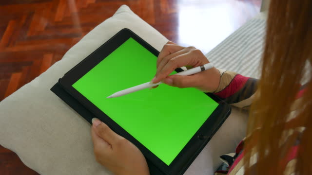 Businesswoman using Digital pen writing note on Digital Tablet green screen