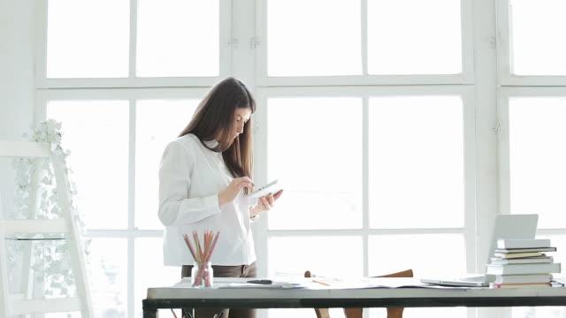 donna d'affari utilizzando compressa digitale e computer portatile nel suo ufficio. - rapporto video stock e b–roll