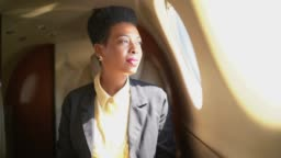 Businesswoman using digital tablet and looking through corporate jet window