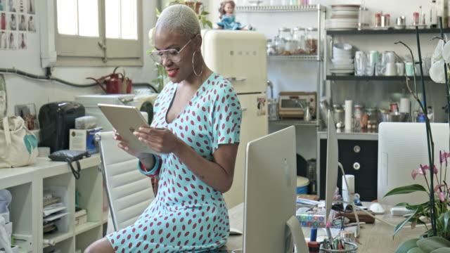 vidéos et rushes de femme d'affaires utilisant la tablette numérique au bureau - agence de design