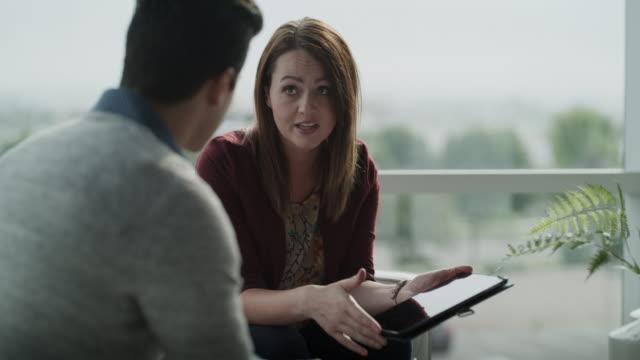 businesswoman using digital tablet for sales presentation with businessman / pleasant grove, utah, united states - über die schulter stock-videos und b-roll-filmmaterial