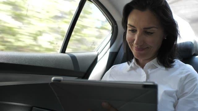 affärskvinna med digital tablett för att arbeta på bil - fordonsinteriör bildbanksvideor och videomaterial från bakom kulisserna