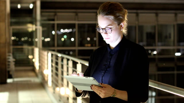 Businesswoman using digital tablet in dark office
