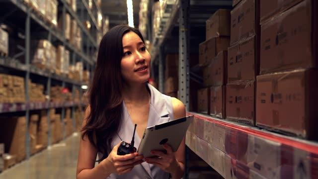 ビジネスウーマンは、流通倉庫でデジタルタブレットを使用しています。 - 貯蔵庫点の映像素材/bロール