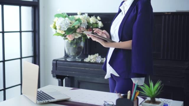 vidéos et rushes de femme d'affaires utilisant la tablette numérique dans son bureau - pavé tactile