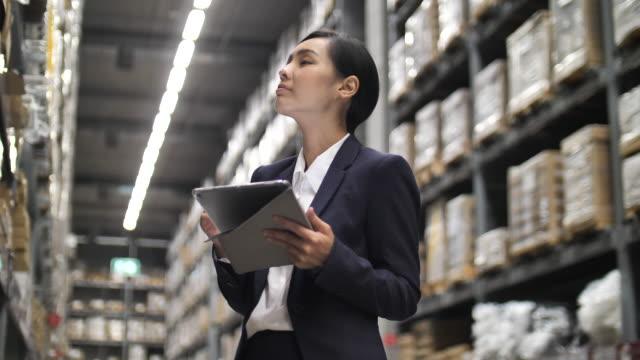 倉庫でデジタルタブレットを使用するビジネスウーマン - 流通センター点の映像素材/bロール