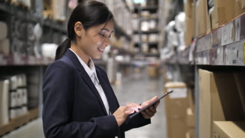 businesswoman using digital tablet in warehouse - electronic organizer stock videos & royalty-free footage