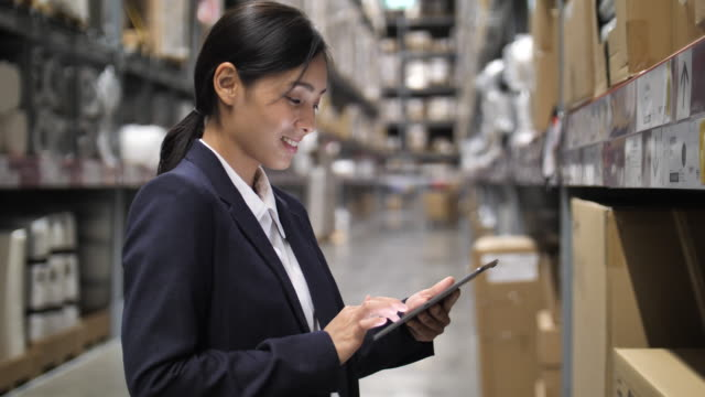 businesswoman using digital tablet in warehouse - electronic organizer stock videos and b-roll footage
