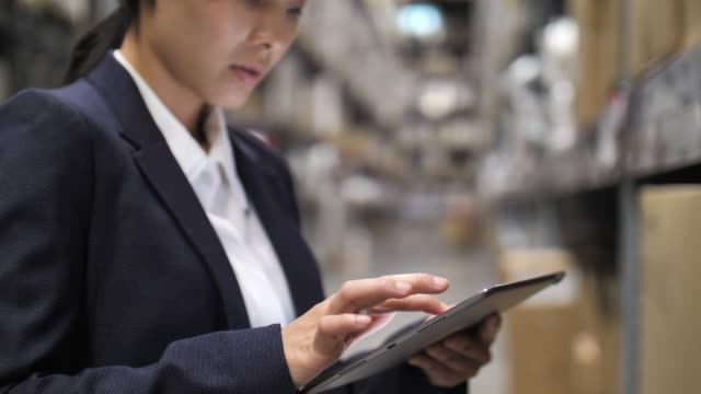vidéos et rushes de femme d'affaires utilisant la tablette numérique dans l'entrepôt - composition graphique