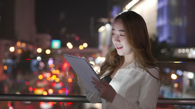 businesswoman using digital tablet on streets by night - 20 24 years stock videos & royalty-free footage