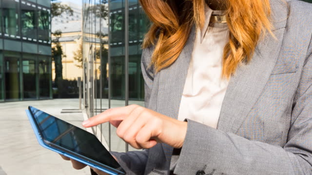 CU Businesswoman using digital tablet outdoors