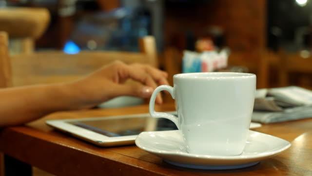 vídeos de stock, filmes e b-roll de mulher de negócios usando tablet digital - xícara de café