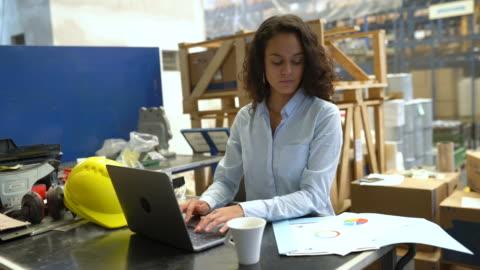 vídeos de stock, filmes e b-roll de empresária usando laptop e verificando um documento no armazém - loja