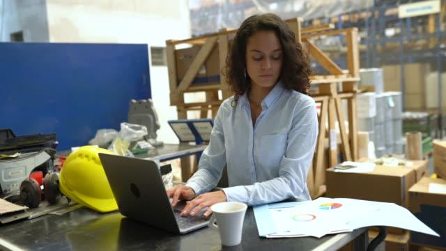 geschäftsfrau mit laptop und überprüfung eines dokuments im lager - distribution warehouse stock-videos und b-roll-filmmaterial