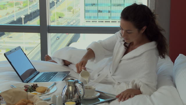 ms pan businesswoman using laptop and drinking tea in hotel room / cape town, cape town, south africa - adagiarsi video stock e b–roll