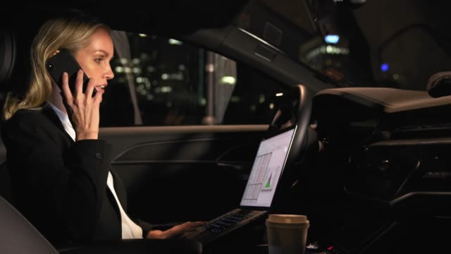 Geschäftsfrau mit Laptop und Handy im Auto