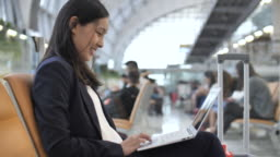 Businesswoman using Laptop at Airport