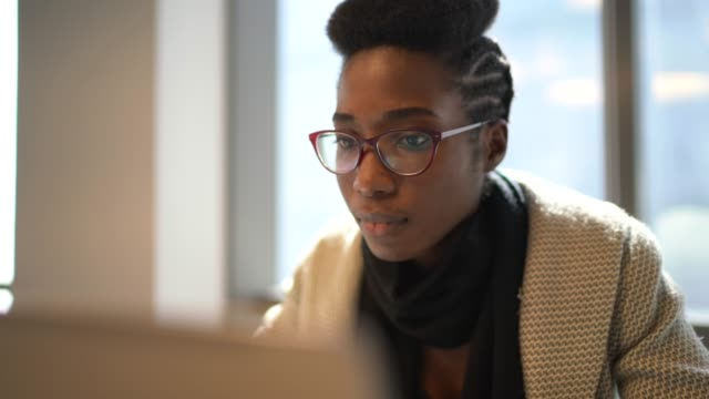 vídeos de stock e filmes b-roll de businesswoman using laptop at work - afro