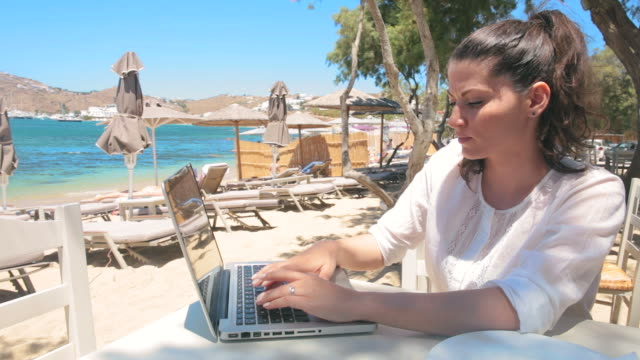 Businesswoman using laptop by the beach.