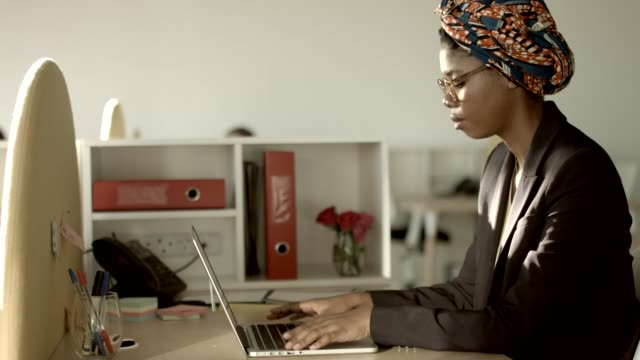 businesswoman using laptop in creative office - headdress stock videos & royalty-free footage