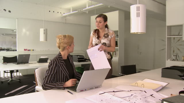 MS Businesswoman using laptop in office when another woman enters with document and begins arguing with her, then manager intervenes and removes angry woman / Berlin, Germany