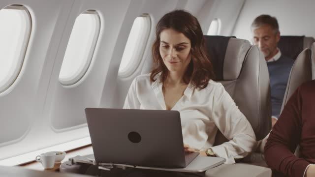 imprenditrice che usa laptop in aereo privato - interno di veicolo video stock e b–roll