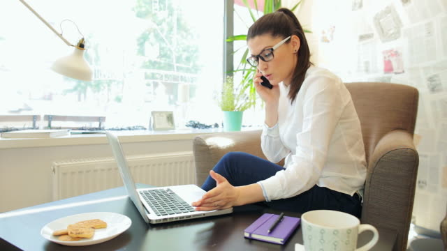 businesswoman using laptop while having a phone conversation. - customer stock videos & royalty-free footage