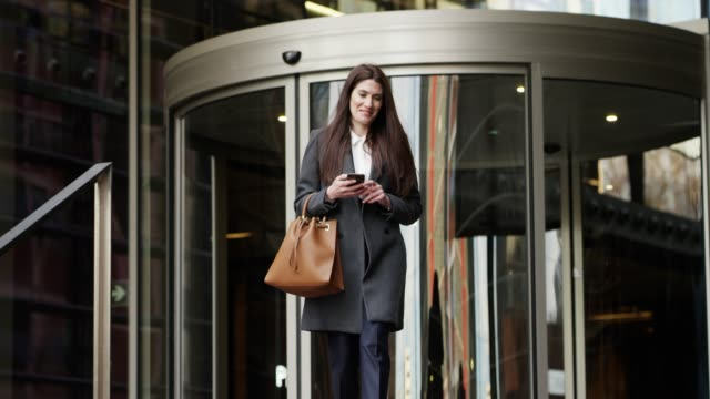businesswoman using mobile phone after work - borsetta video stock e b–roll