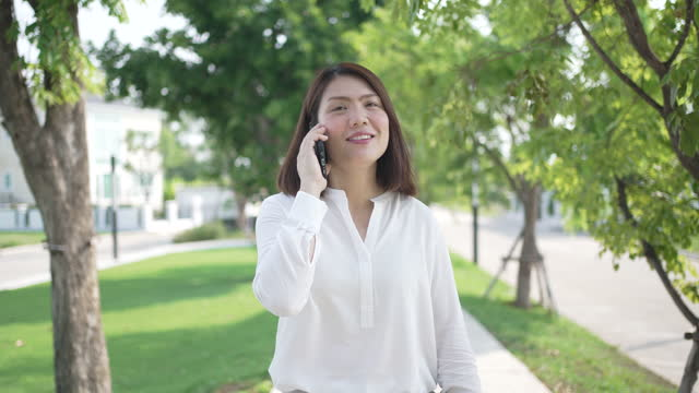 businesswoman using mobile phone and walking in public park in break after lunch time - formal stock videos & royalty-free footage