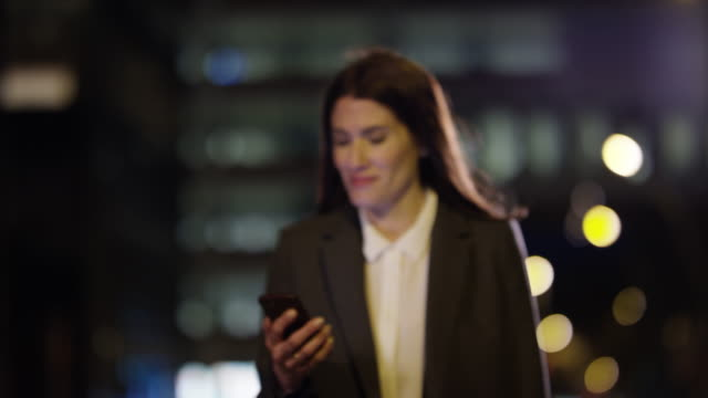 businesswoman using mobile phone at night in city - quarantenne video stock e b–roll