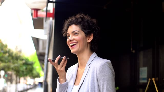 businesswoman using mobile phone in front of the hotel - short hair stock videos & royalty-free footage