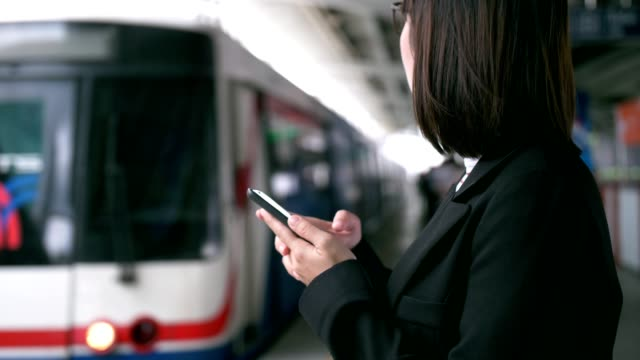 businesswoman using mobile phone while waiting for train - railway station platform stock videos and b-roll footage