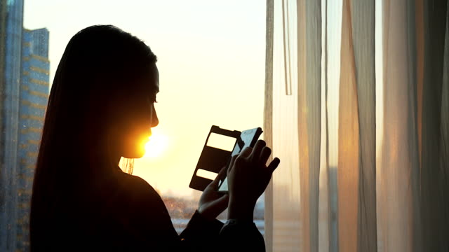 Businesswoman using mobile phone with silhouette scene.