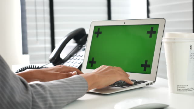 Businesswoman using on computer laptop in office with green screen