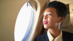 Businesswoman using phone and looking through corporate jet window