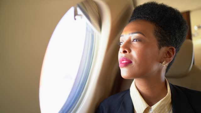 businesswoman using phone and looking through corporate jet window - daydreaming stock videos & royalty-free footage
