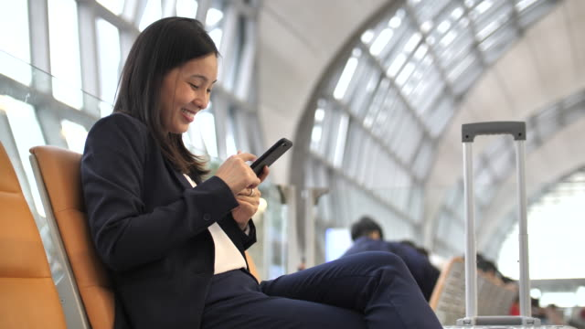 businesswoman using phone at airport - business travel stock videos & royalty-free footage
