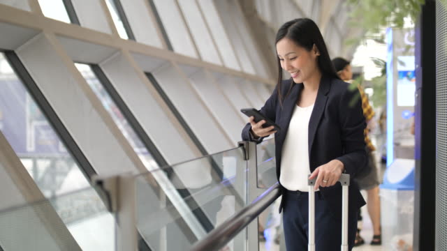 businesswoman using phone at airport - businesswoman stock videos & royalty-free footage