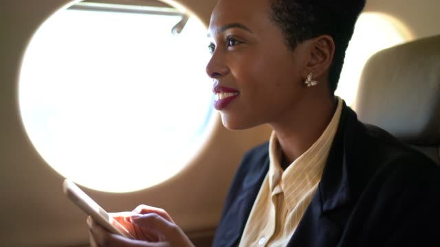 businesswoman using phone in a corporate jet - business travel stock videos & royalty-free footage