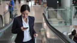 Businesswoman using phone on escalator at Airport