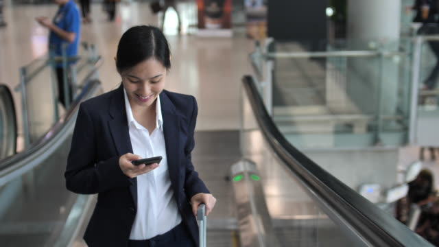 businesswoman using phone on escalator at airport - escalator stock videos & royalty-free footage