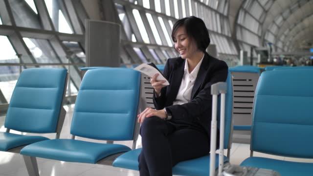 vídeos de stock, filmes e b-roll de mulher de negócios que usa o aeroporto esperto do telefone - mulher de negócios