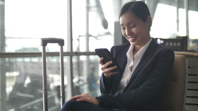 businesswoman using smart phone at airport, business travel - business travel stock videos & royalty-free footage