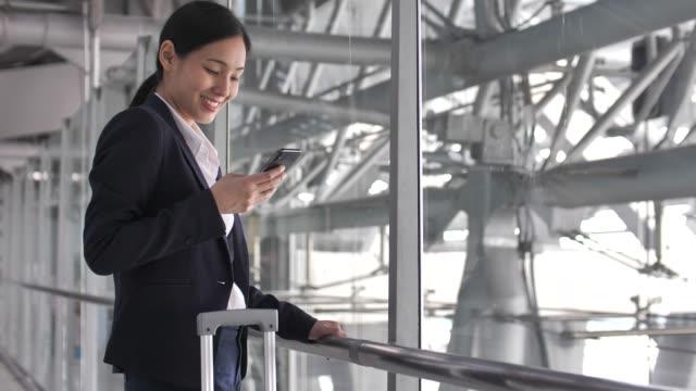 vídeos de stock, filmes e b-roll de mulher de negócios que usa o telefone esperto no aeroporto para o curso de negócio - estação