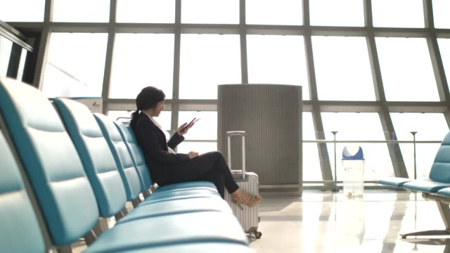 businesswoman using smart phone at airport - multimedia stock videos & royalty-free footage